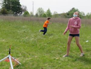 Students look up to track their rockets after launch.