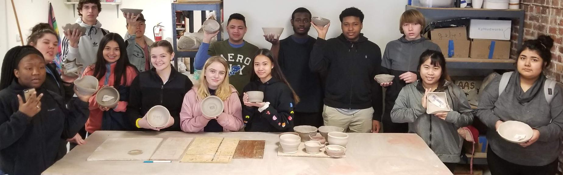 students holding up pottery they made at Pocosin Arts