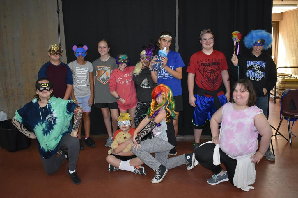 Students posing in a photo booth with props