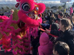 Students feeding the dragon red envelop for good luck.