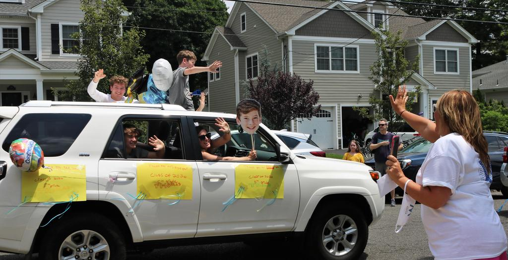 Photo of Wilson teacher waving enthusiastically at family (waving back) in Grade 5 Clap Out Car Parade.