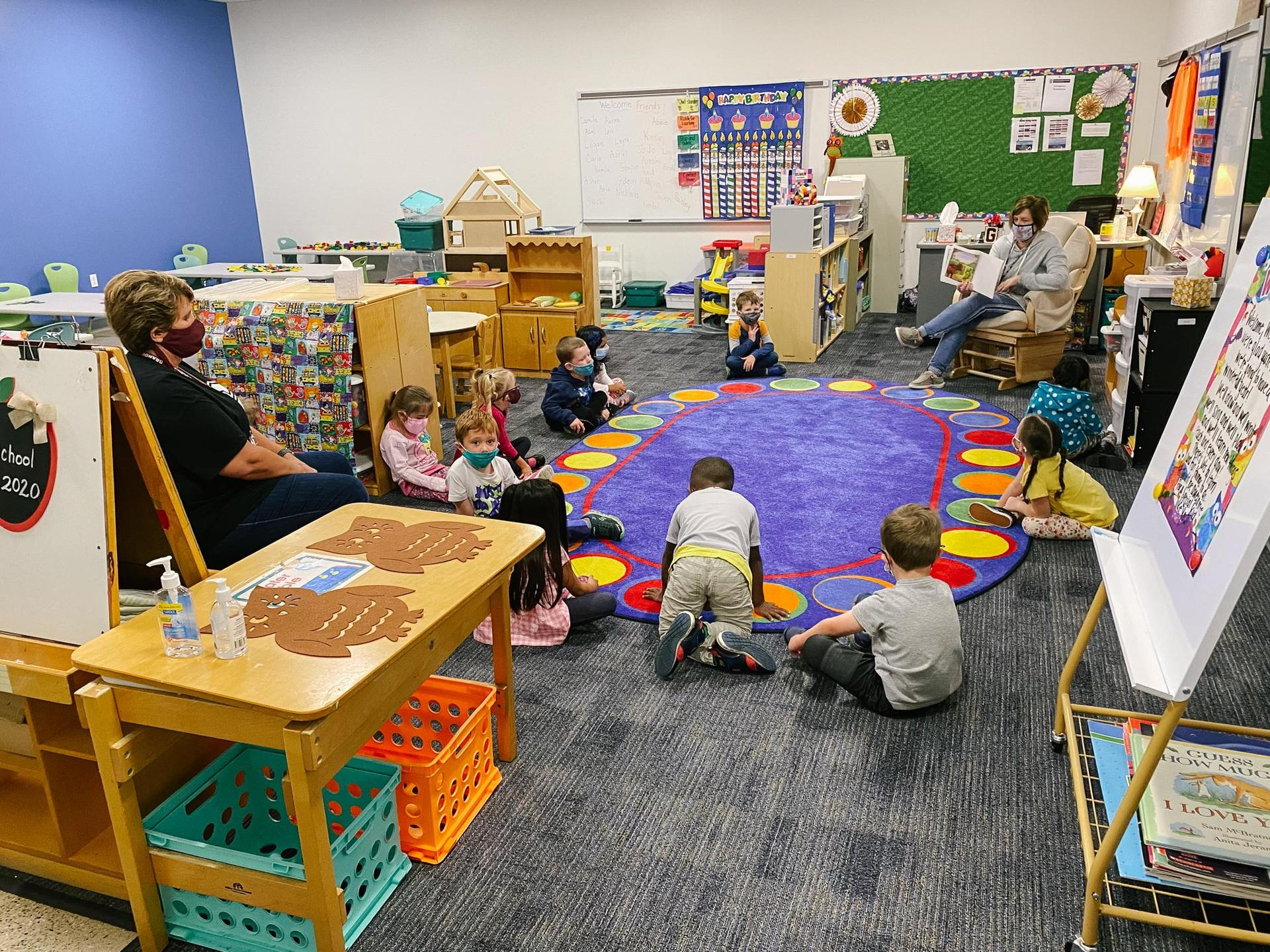 preschool kids on the floor on a rug sit on a circle with masks on
