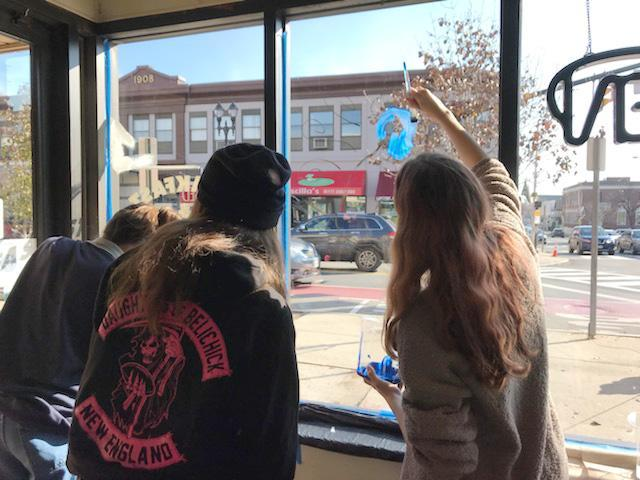 The view from the inside of a business as two students decorate a window, with a view of Everett Square in the background