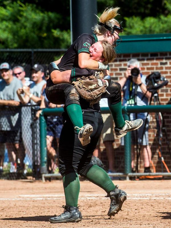 Coloma first baseman Hannah Mathis leaps high into the arms of teammate and third baseman Samantha Stewart after winning the Division 3 championship softball game on Saturday, June 16, 2018 at Michigan State University's Secchia Stadium in East Lansing.