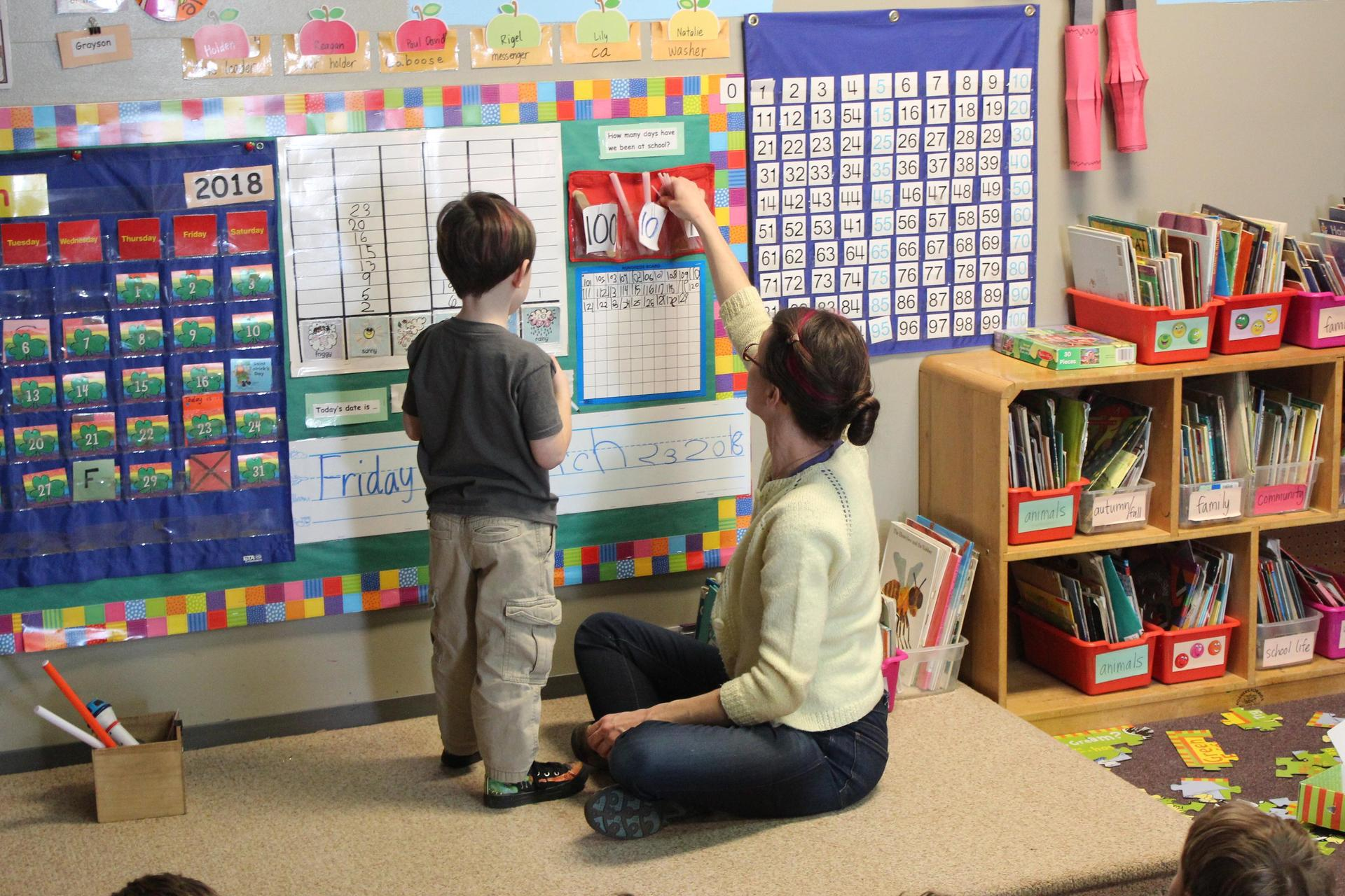 A teacher assists student at the front of class