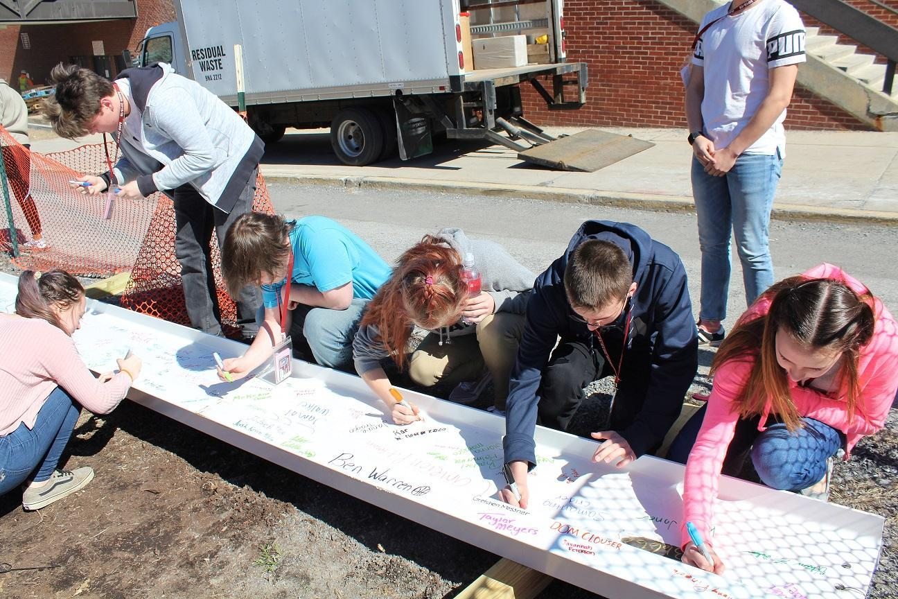 Students signing final steel beam