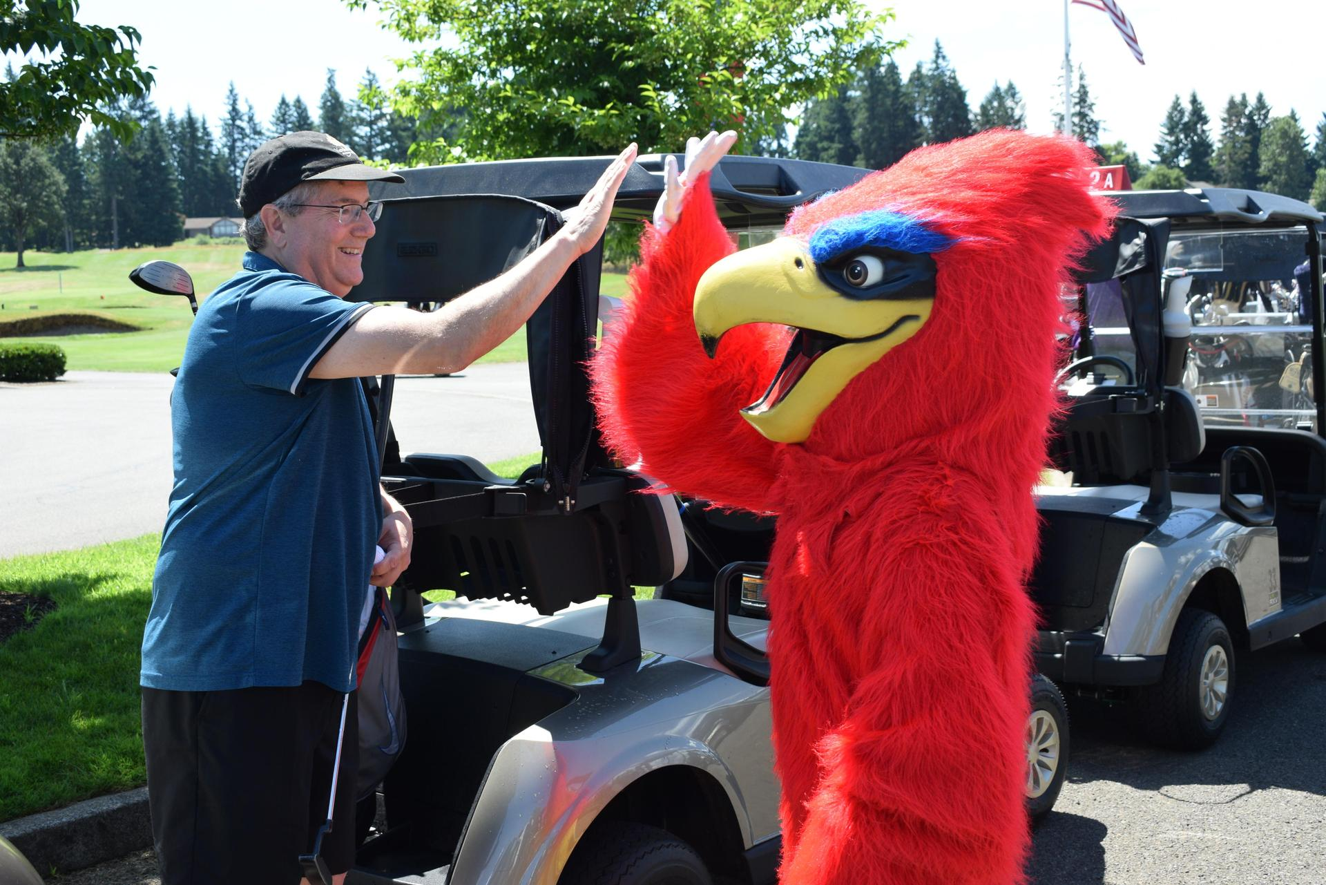falcon mascot high fives golfer