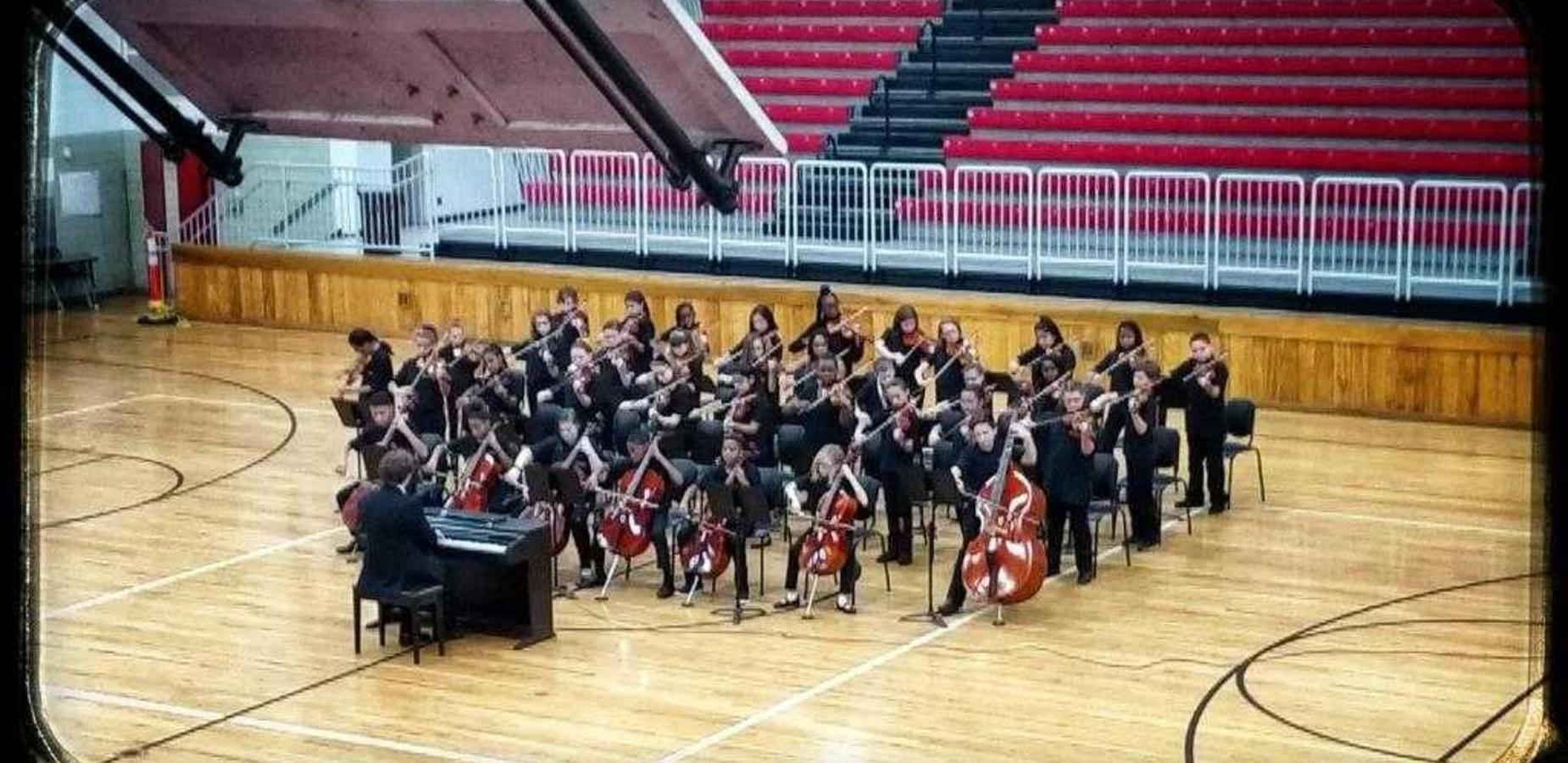 A photo of the Creekside Middle School orchestra performing during a school concert.