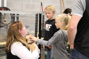 Pathways staff holding rabbit for children to pet