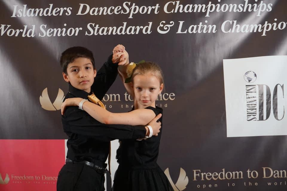 boy and girl standing in front of the Islander DanceSport Championship Banner in Dance pose