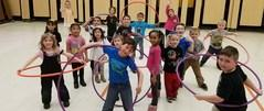Elementary students using a hula hoop