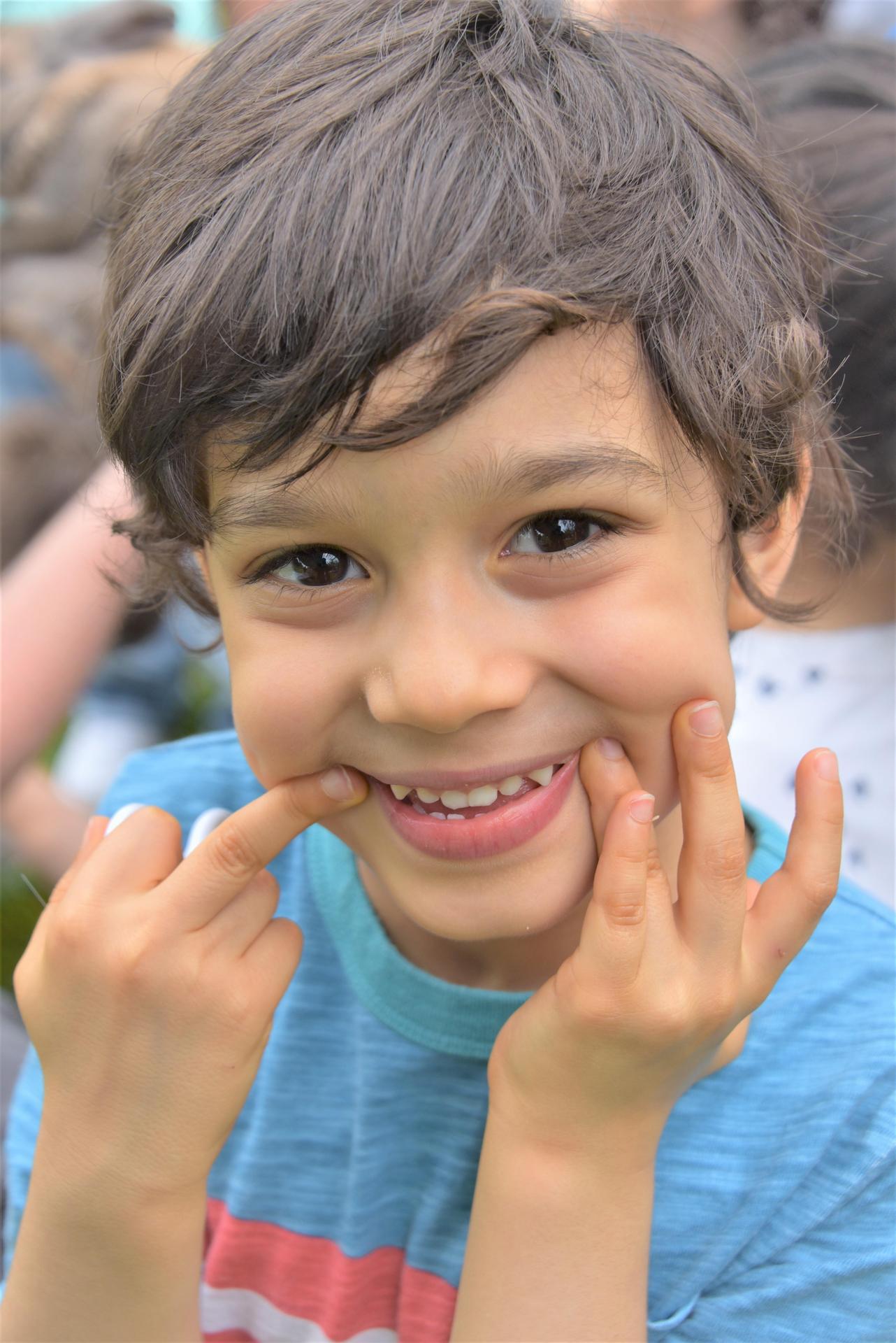 A boy comes close to a camera and smiles.