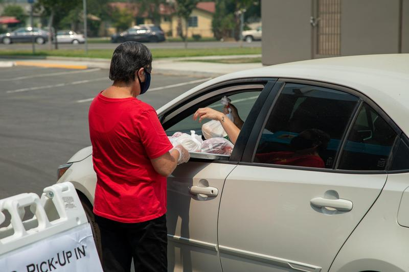KHSD Nutrition Services employee distributing meals to a driver