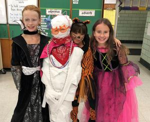 Three students show off costumes during a Halloween party in their classroom at Washington School.