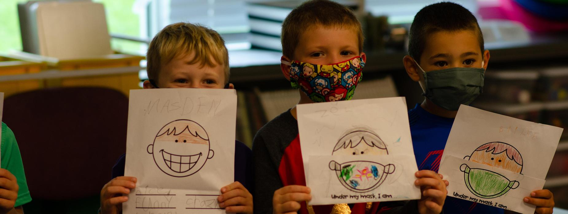 Students holding up their drawings of why they wear masks
