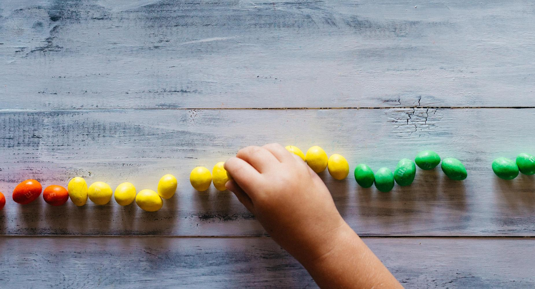 a child's hand sorts peanut m&m's by color on a wooden table