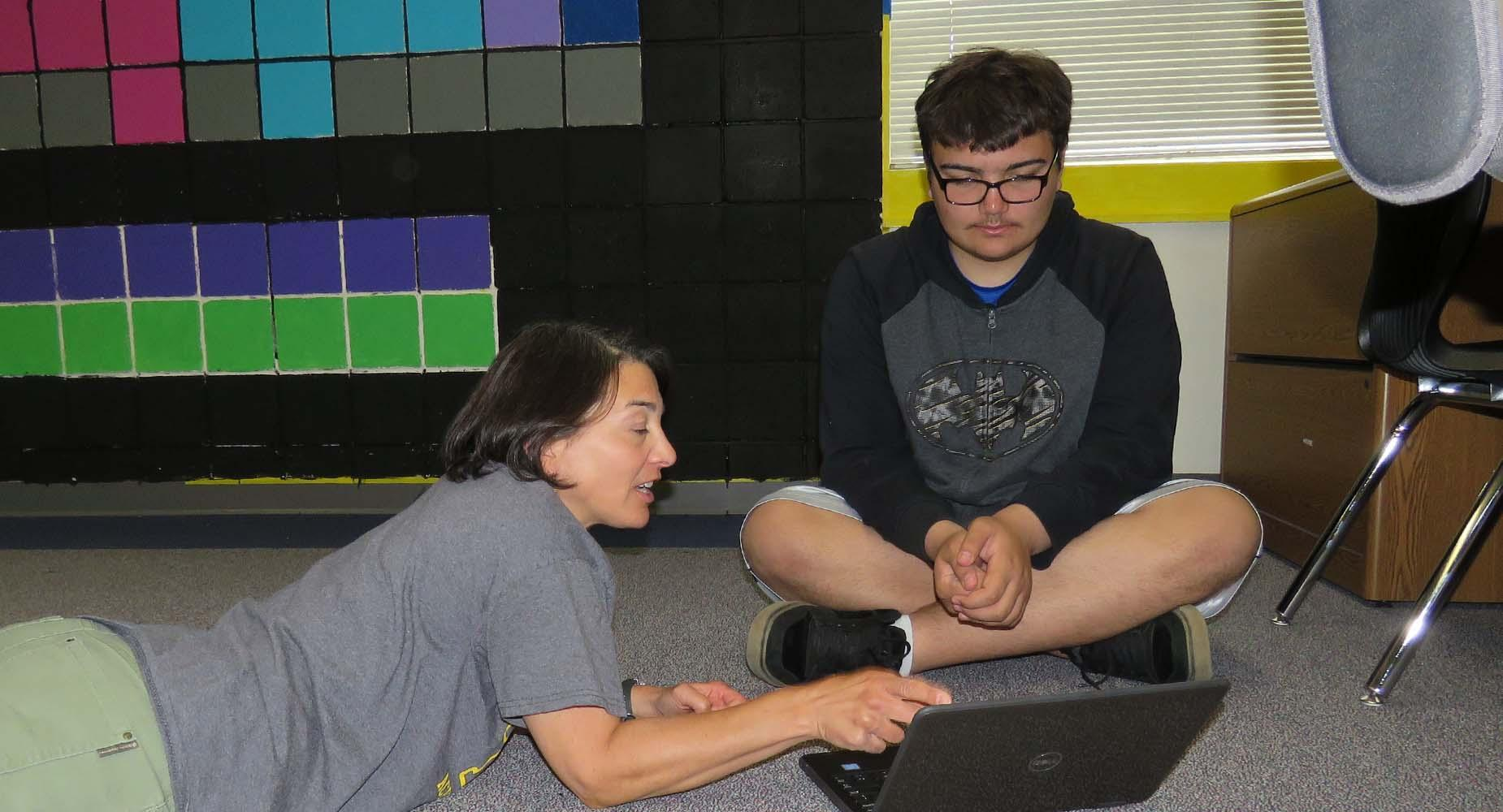 Teacher lays of floor and points to laptop while student watches, cross-legged on the floor.