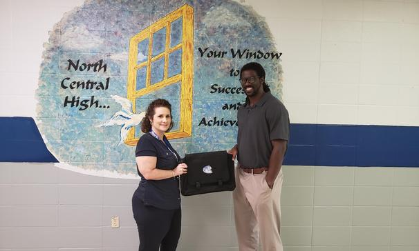 Mr. Arnold Gore, a first-year middle school mathematics teacher at North Central High School, receives a PBIS reward from Mrs. Brandi Reed, assistant principal, for being an exemplary employee.