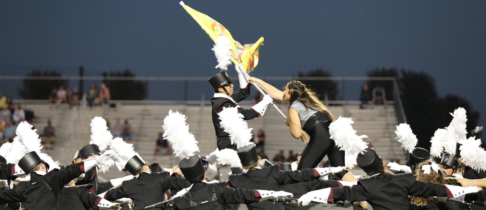 marching band students encircle two who are grabbing band flag on field
