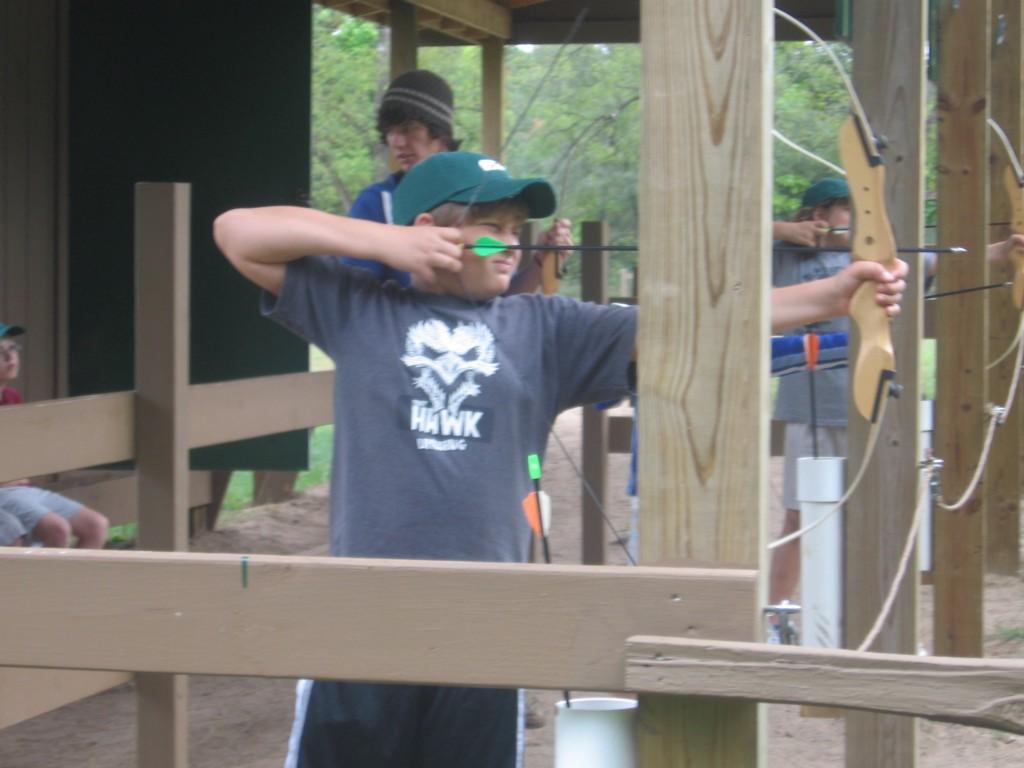 boy shoots arrow at camp