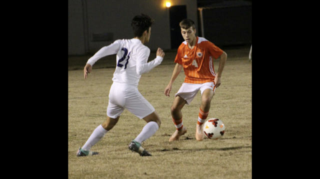 Gavin D. kicking the soccer ball.