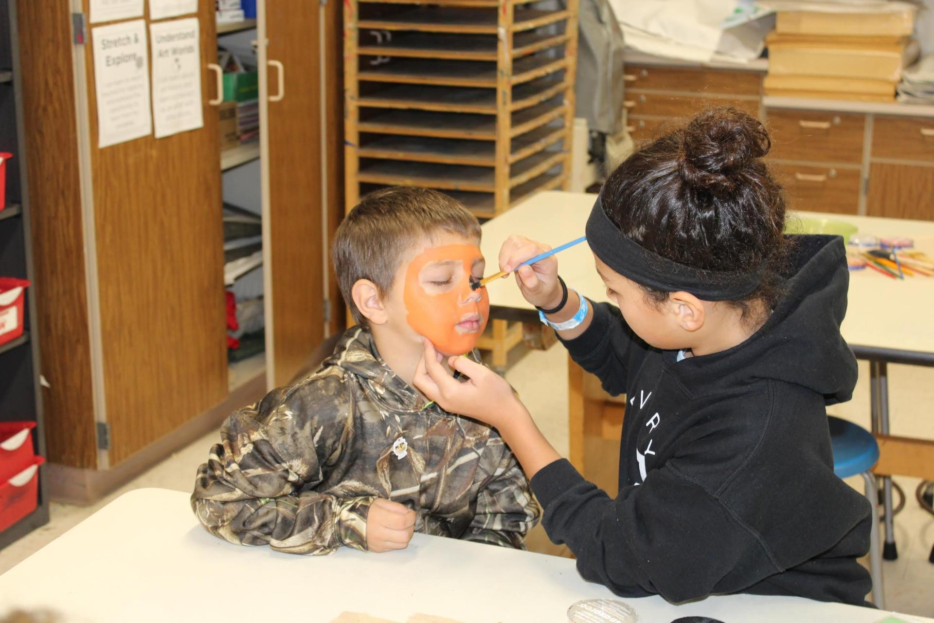 Student painting another students face during fall festival.