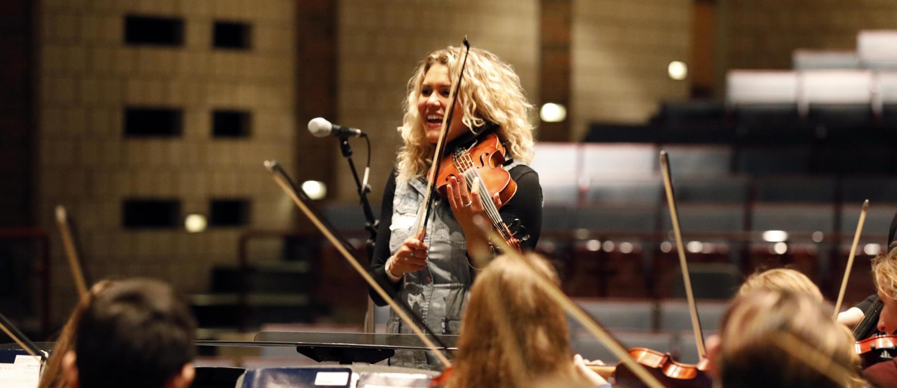 orchestra teacher smiles in auditorium teaching violinists