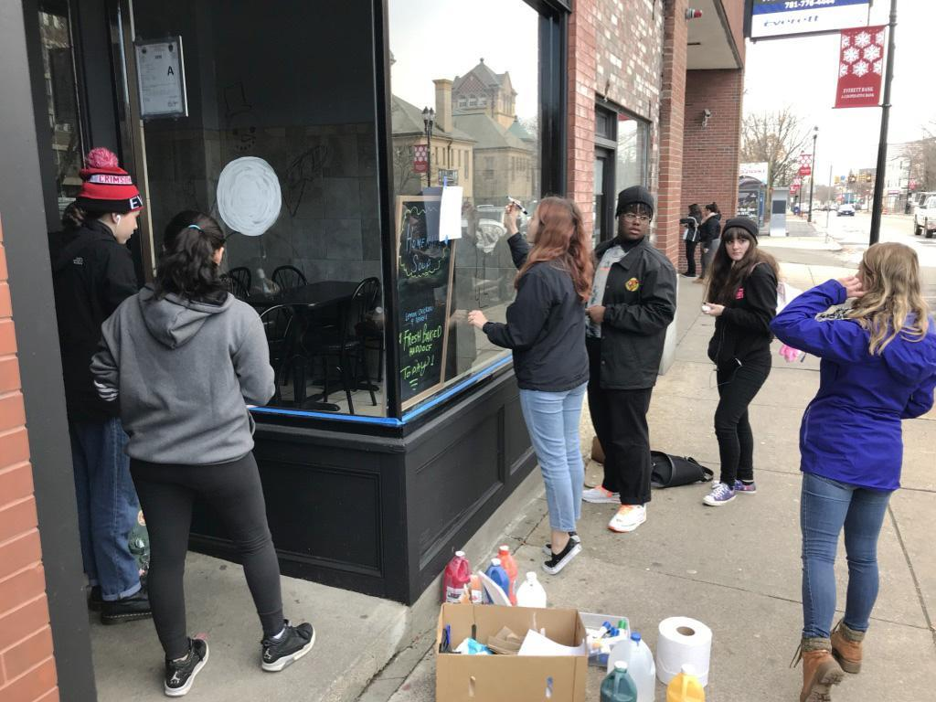 A group of five students decorate a store window, as teacher Annette LeRay overlooks their work