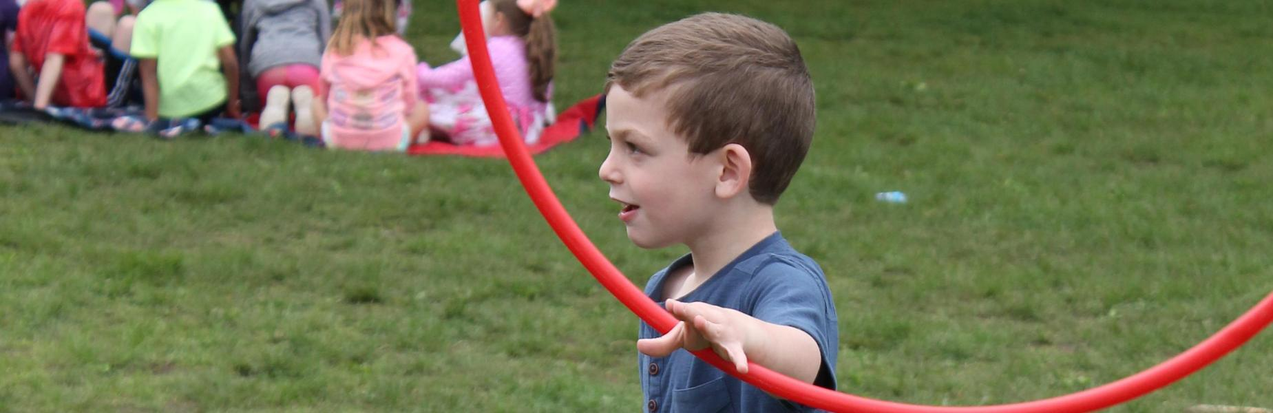 Kindergartner plays with hoola hoop.