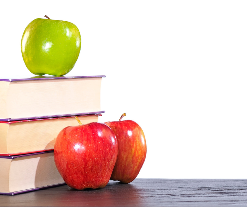Three books are on a table, there is a green apple on top of the books and two red apples in front of the books.