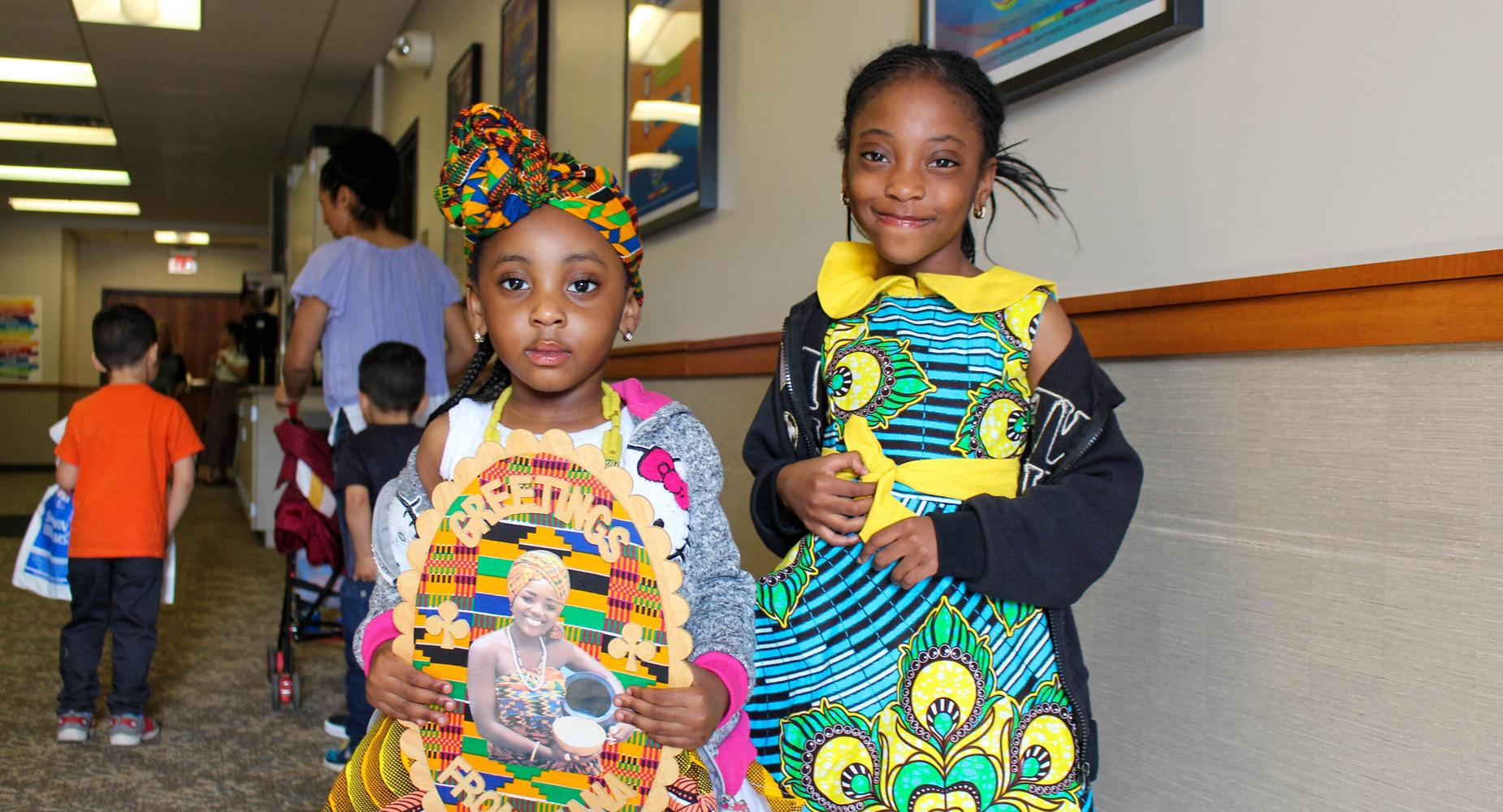 Two Black girls smile for the camera while proudly displaying their traditional dresses and head garments