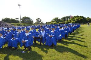 Boys, dressed in royal blue gowns, listen as their principal addresses the class.