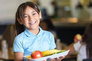 Smiling girl with lunch tray