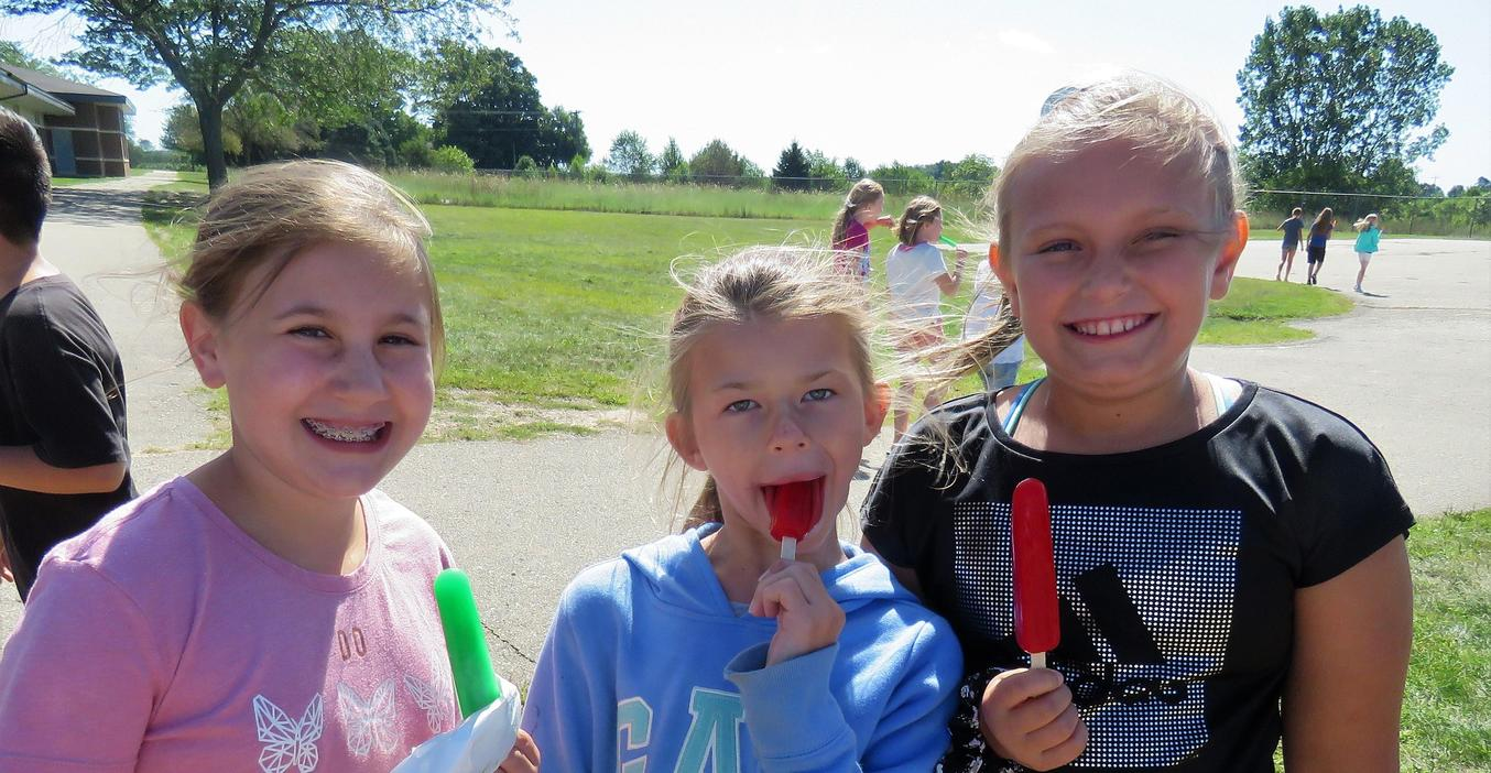 Students enjoy popsicles on the playground.