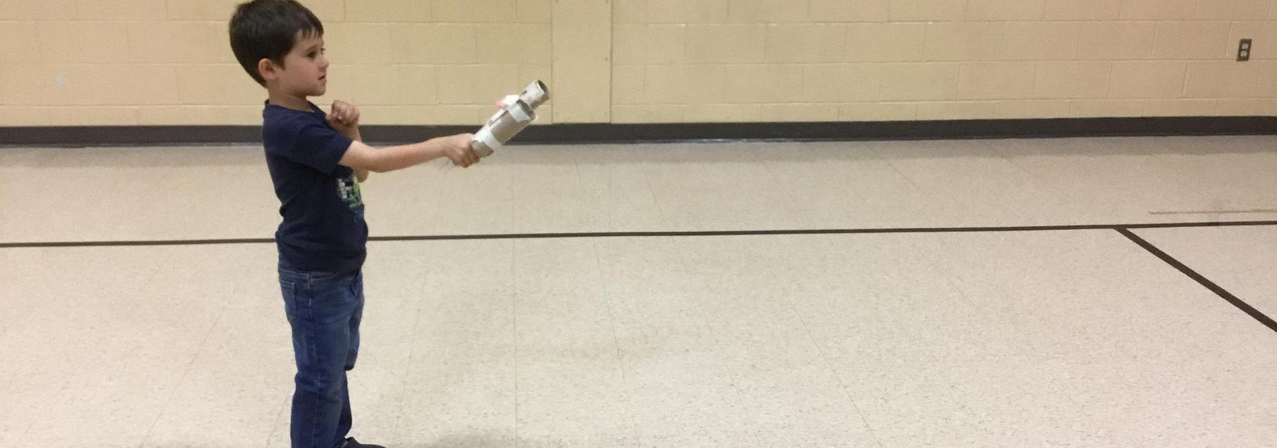 boy holding a device that launches objects in gymnasium