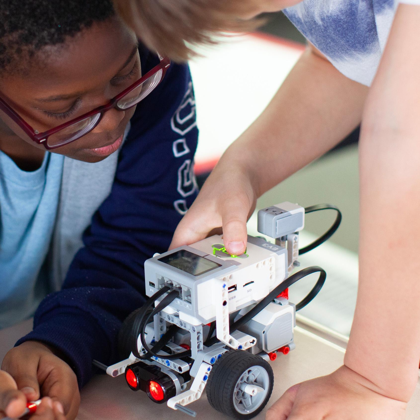 two students program a lego coding brick