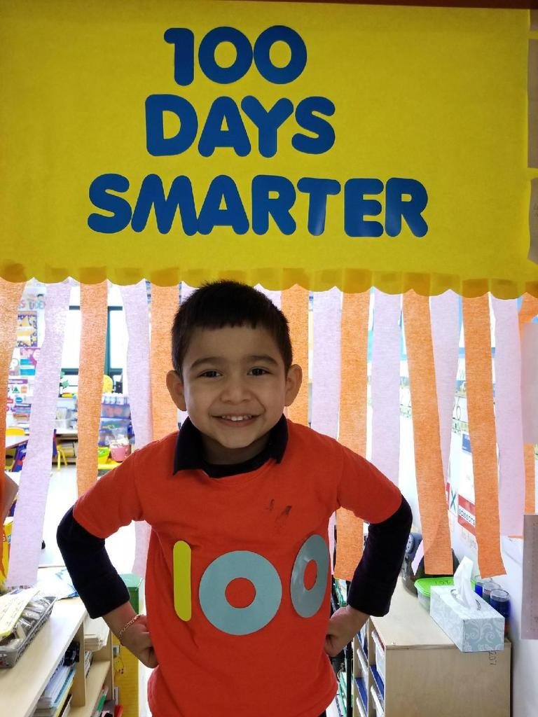 boy posing under sign celebrating 100 days of school
