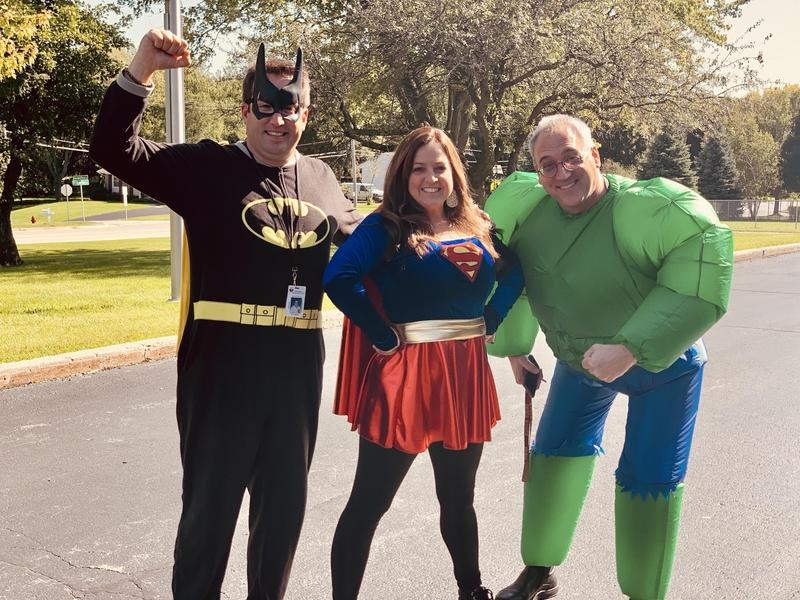 Principals dressed as Batman, Supergirl, and the Hulk