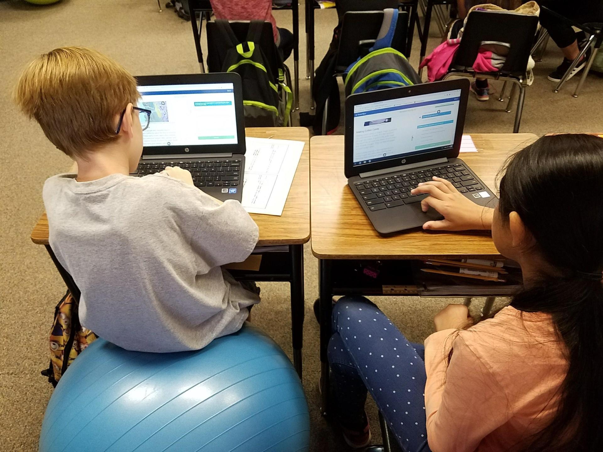 students on balance balls using computers