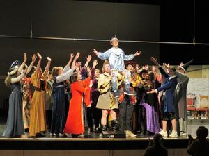 The cast rehearses one of the songs as Prince Dauntless is lifted high on the shoulders of those in the kingdom.