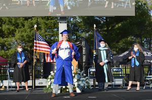Graduate dressed in blue opens his gown to show his baseball uniform top poses after receiving his diploma