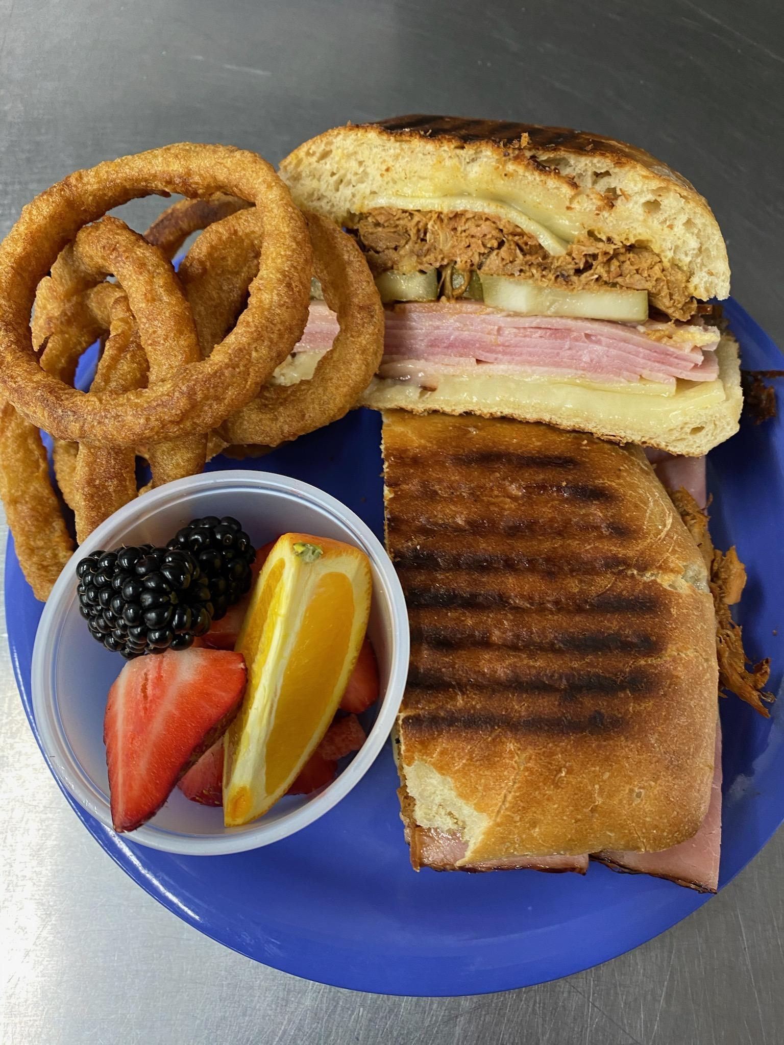 cuban sandwich with onion rings and fruit
