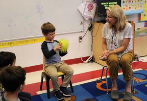 Photo of Lincoln preschool teacher and student exchanging ball and compliments during a Week of Respect game.