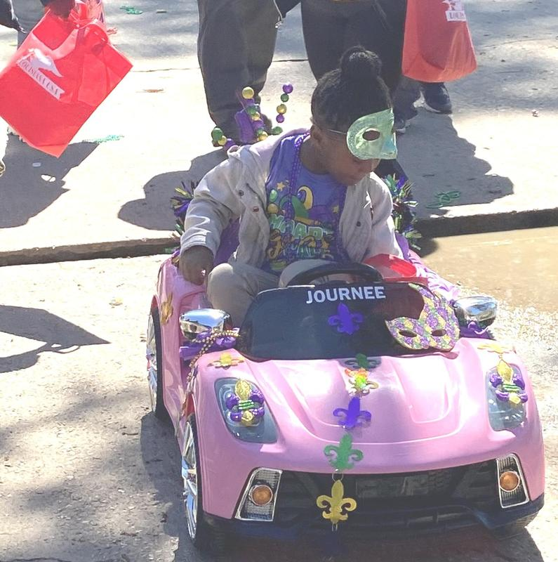a young Mardi Gras student riding in his car during the PRAMS 2020 Mardi Gras parade