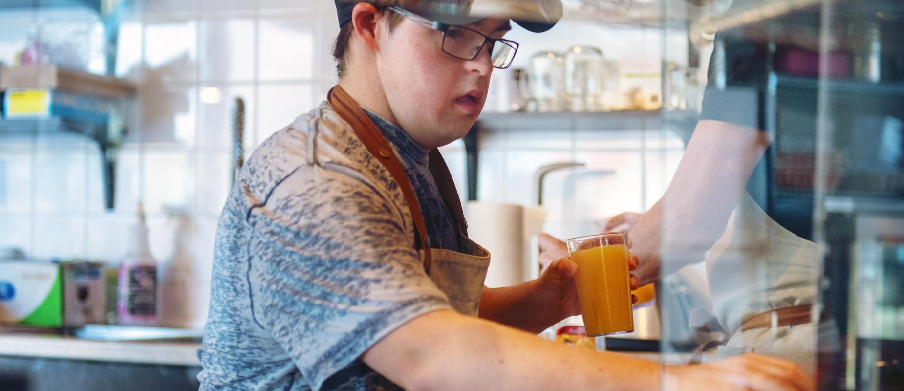 boy with Down's Syndrome working in a coffee shop