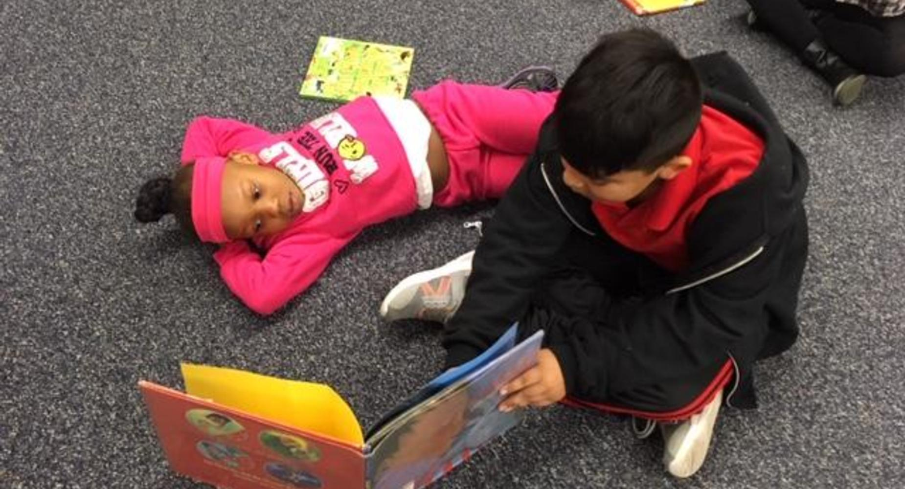 World read aloud day with Cubby Buddies. A 3rd grader reads to his kindergartner buddy.