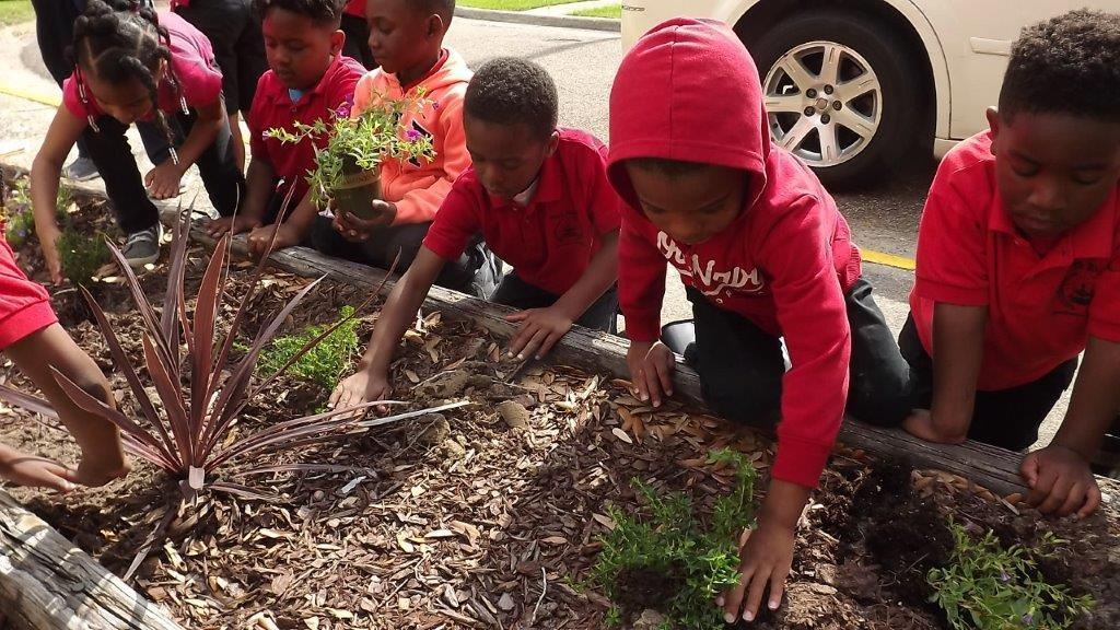 A photo of Park Ridge kindergarten student or students working to beautify the school's flower beds