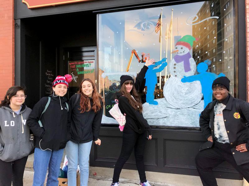 Five students stand in front of a window decorated with a painting of children making a snowman