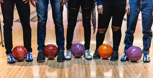 Legs of five people wearing bowling shoes holding bowling balls with their feet