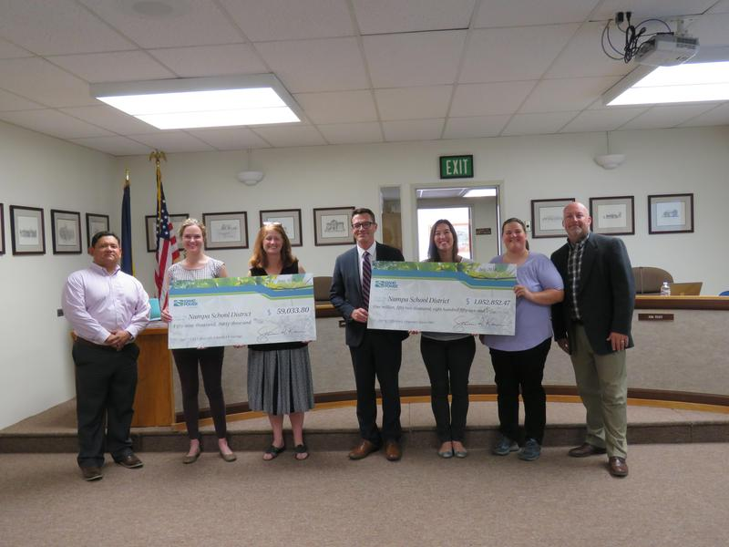 Idaho Power Reps present incentive checks to the Board.